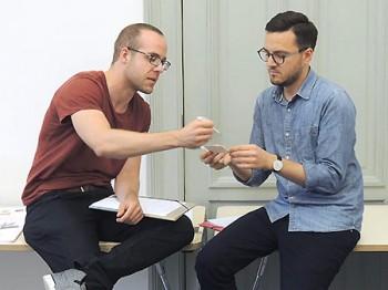 zwei Teilnehmer im Training betrachten und diskutieren Visitenkarten