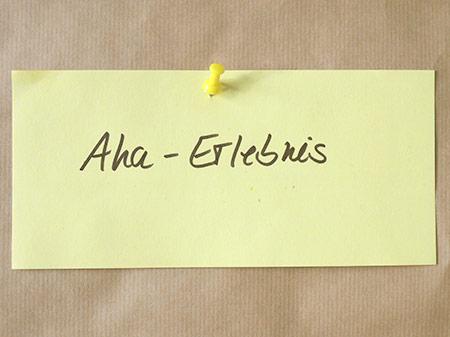 Moderationskarte an Metaplanwand, auf welcher »Aha-Erlebnis« steht