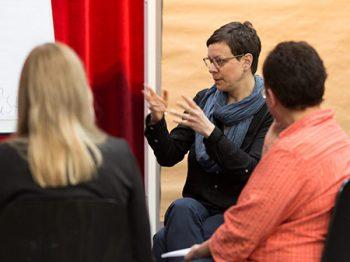 Workshop-Moderatorin Esther Schaefer macht eine Handbewegung, Profil