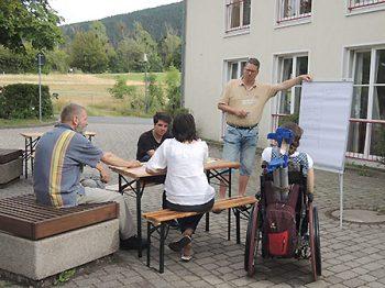Personengruppe arbeitet am Flipchart auf dem Hof draußen, darunter Frau im Rollstuhl