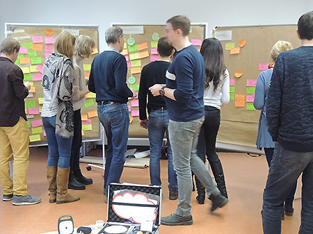 Workshop-Moderation: Gruppe an Pinnwänden mit bunten PostIts