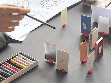 Wachsstifte und kleine Pappen mit Hand bei Ideenworkshop