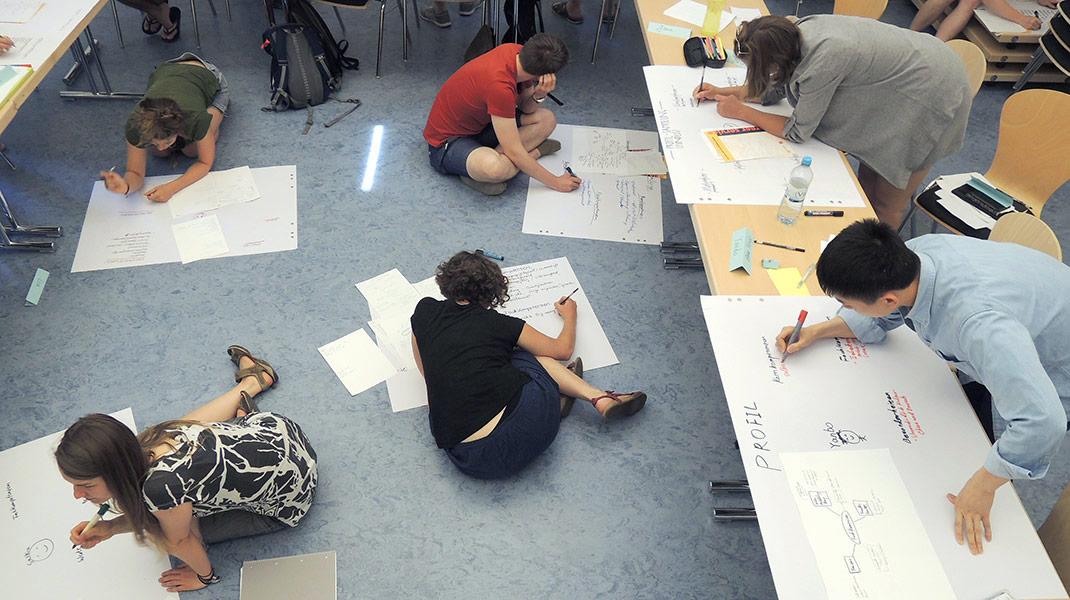 Workshop-Teilnehmer/innen arbeiten auf dem Boden und an Tischen