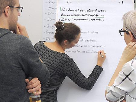 drei Personen probieren im Training kreativitaetstechniken am Flipchart aus
