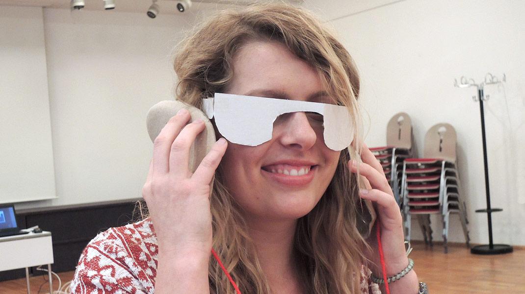 im Design Thinking-Training: Frau mit Brille aus Pappe und Papp Hörgeräten
