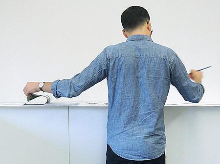 Teilnehmer steht am Tisch, blättert in einem Heft und mach dabei Notizen