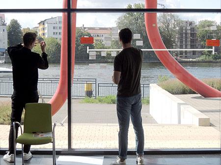 zwei Teilnehmer arbeiten an einer Timeline auf Fensterscheibe an der Spree
