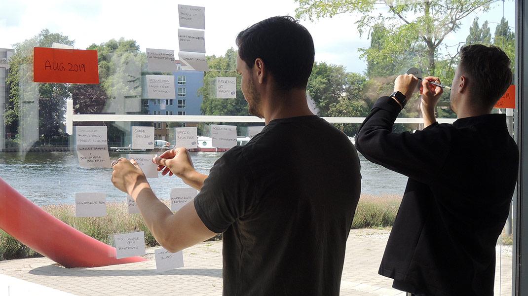 zwei Teilnehmer notieren Meilensteine auf einer Timeline an einer Fensterscheibe mit Blick auf die Spree