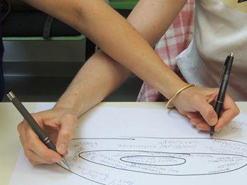 zwei arme kreuzen bei der zusammenarbeit sich über einem papier